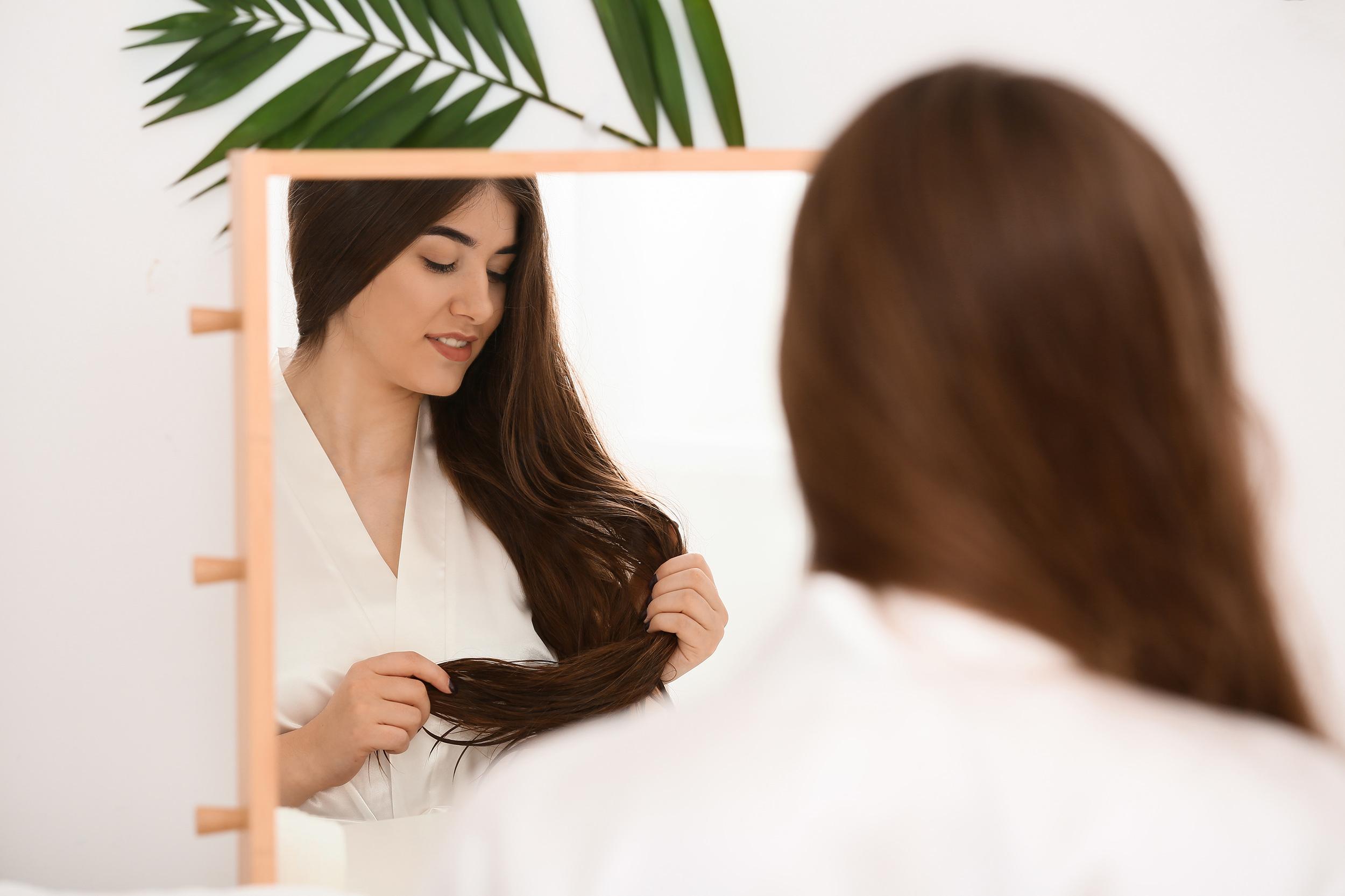 Ruskeahiuksinen nainen peilaa itseään peilistä ja harjaa hiuksiaan