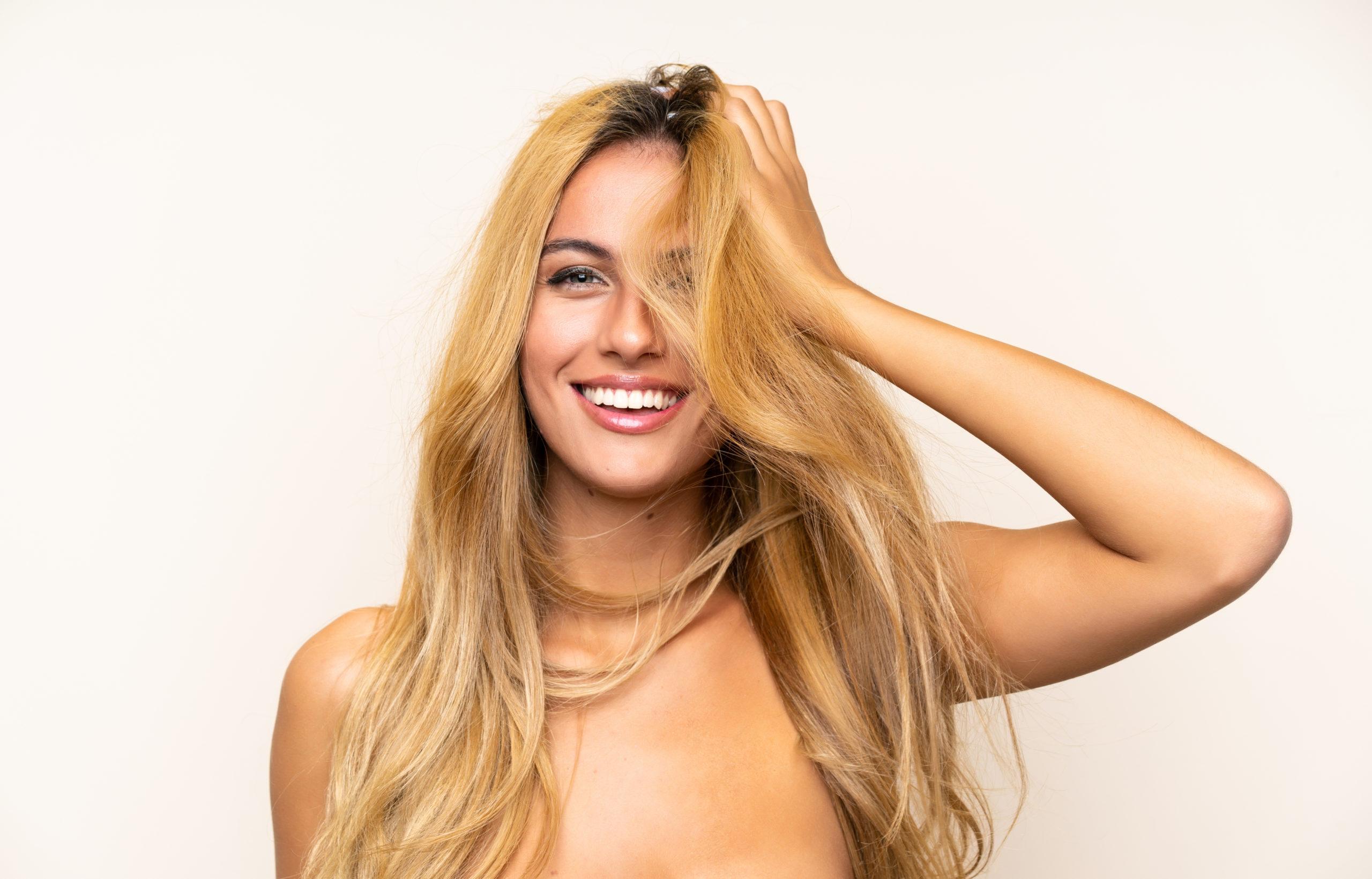 Vaaleahiuksinen nainen pöyhii pitkiä hiuksiaan
